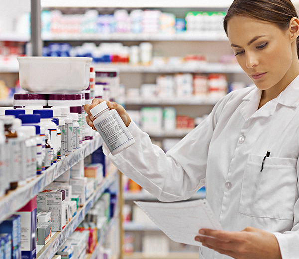 Pharmacist holding pill bottle and reading paper - OCEASOFT